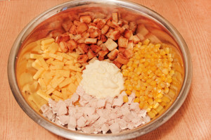 Смешайте курицу, сухарики, сыр и кукурузу