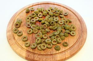 Оливки нарежьте колечками