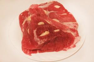 Поместите чеснок в надрезы в мясе